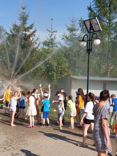 Strażacy oblewają wodą dzieci z wozu strażackiego na dniu dziecka w Jaczkowie